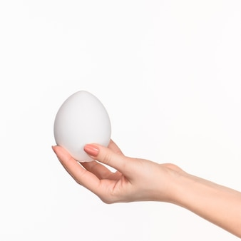 Female hand holding white blank styrofoam oval against the white background with right shadow