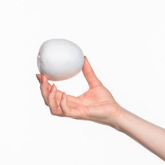 La mano femminile che tiene ovale di polistirolo bianco vuoto contro lo sfondo bianco.