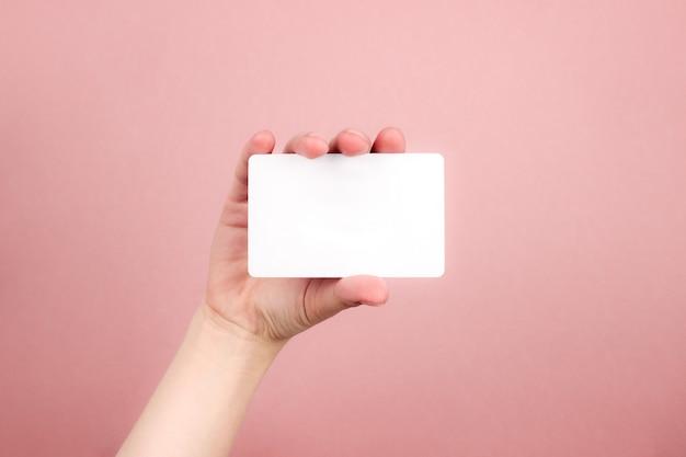 白い名刺を持っている女性の手