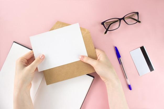 Женская рука держит белую карточку. альбом для рисования, очки, плоская планировка кредитной карты
