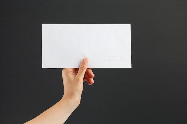 Female hand holding a white envelope on black background