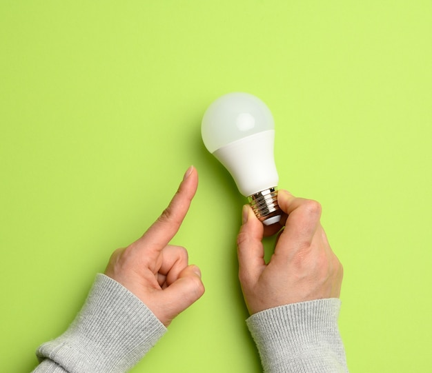 Female hand holding white glass lamp, green energy, close up