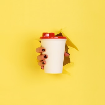 Female hand holding white paper mug on yellow background.