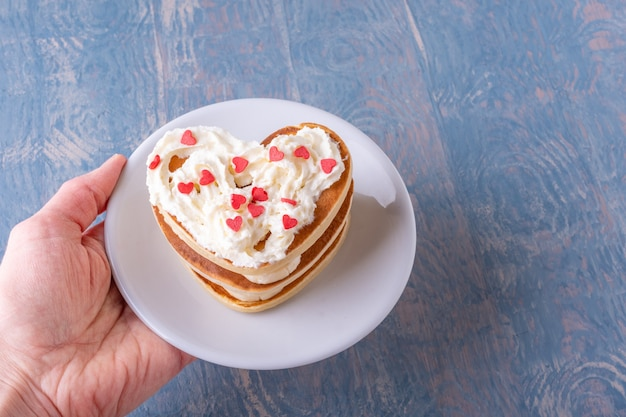 Female hand holding a white plate with a stack of homemade heart shaped pancakes decorated with white cream with red hearts on a blue wooden background