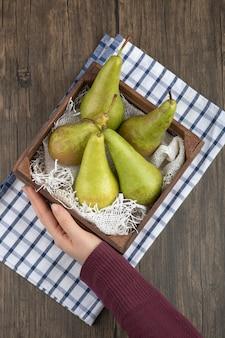 나무 배경에 맛있는 익은 배 나무 상자를 들고 여성 손