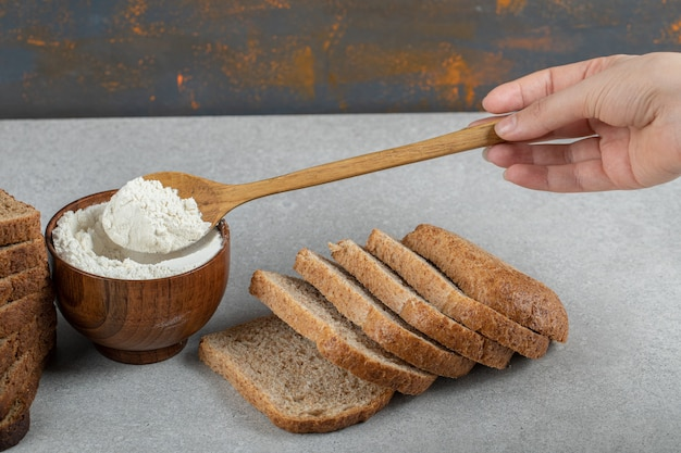 Female hand holding a wooden spoon of flour and slices of bread.