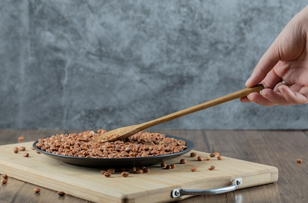 Female hand holding wooden spoon of red beans.