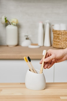 浴室の白いカップに木製の歯ブラシを持っている女性の手