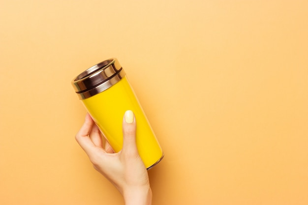 Female hand holding a yellow empty thermocup for drinks on a warm yellow background