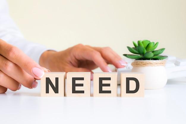 Женская рука держит блок с буквой n от слова need. слово находится на белом офисном столе на фоне белой клавиатуры. финансовые, маркетинговые и бизнес-концепции