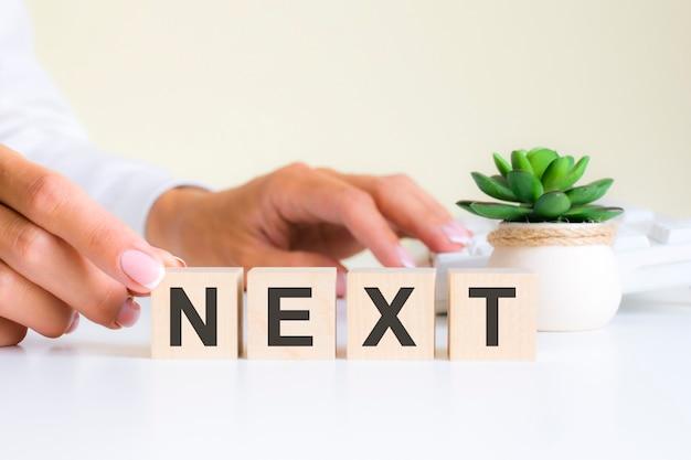 女性の手は、nextという単語の文字nのブロックを持っています。単語は白いキーボードの背景にある白いオフィスのテーブルにあります。財務、マーケティング、ビジネスの概念
