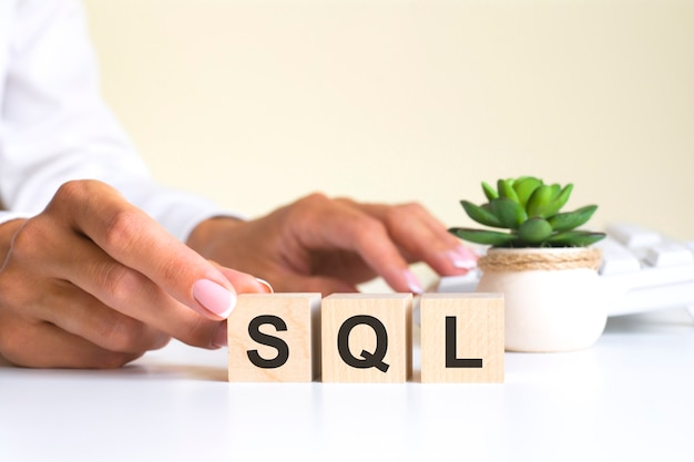 Женская рука держит блок с буквой s от слова sql. слово находится на белом офисном столе на фоне белой клавиатуры. sns - социальная сеть