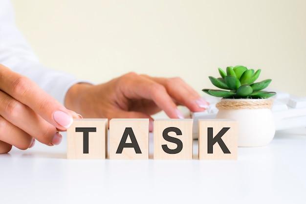 Женская рука держит блок с буквой т от слова задача. слово находится на белом офисном столе на фоне белой клавиатуры. финансовые, маркетинговые и бизнес-концепции