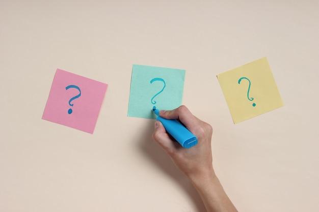 女性の手は青いフェルトペンを持ち、メモ用紙に疑問符を描きます