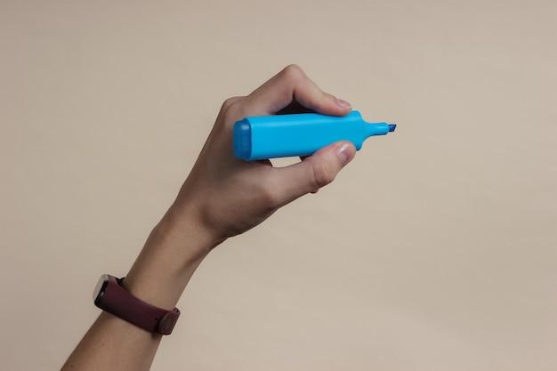 女性の手は黄色のパステル紙に青いフェルトペンを持っています