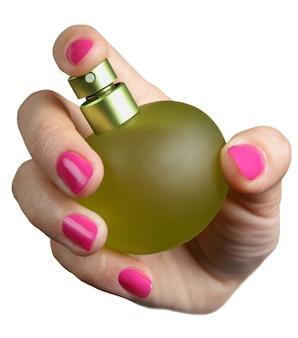 女性の手は白い背景で隔離の香水のボトルを保持します。