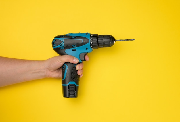 여성의 손은 노란색 배경에 무선 드릴을 들고 있습니다. 작업용 도구