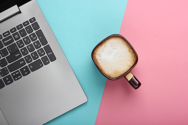 女性の手はカプチーノのカップを保持し、ピンクブルーのパステルカラーの背景にラップトップを使用します。フリーランスのコンセプト、ワークスペース、オンライン作業。上面図