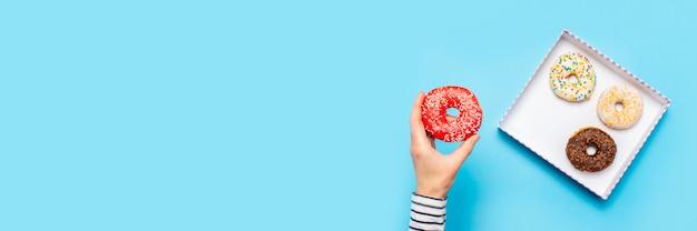 女性の手は青い上にドーナツを持っています。コンセプト菓子店、ペストリー、コーヒーショップ