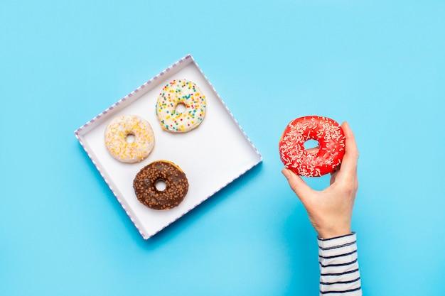 Женская рука держит пончик на синем. концепт кондитерский магазин, выпечка, кофейня.