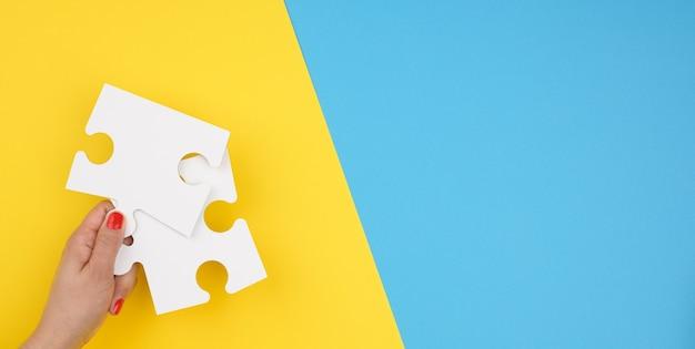 女性の手は、青い背景に白い大きなパズルの断片、アイデアを見つけ、問題を解決するという概念を持っています