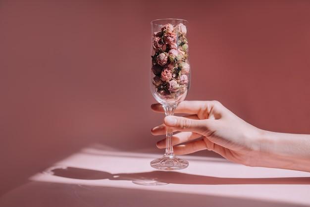 Женская рука держит бокал вина с сушеными розами на розовом