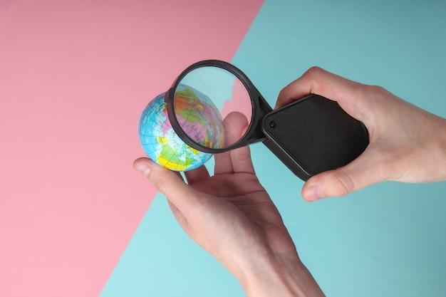 여성 손 블루 핑크 파스텔 배경에 돋보기와 지구본을 보유하고 있습니다. 여행, 관광 컨셉