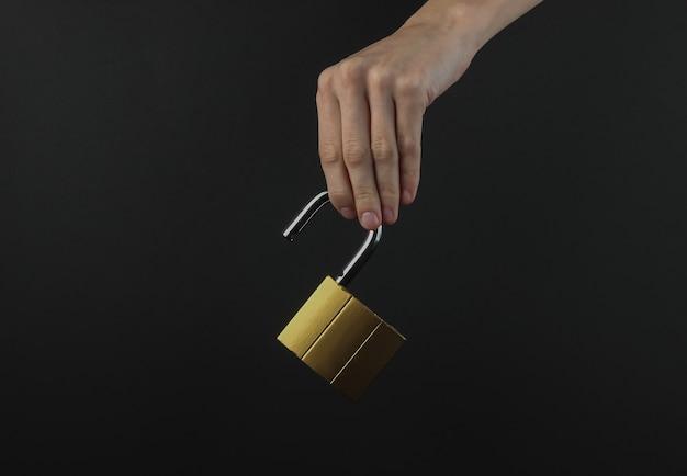 여성 손 검은 배경에 열쇠로 자물쇠를 보유