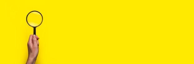 여성 손은 노란색 표면에 돋보기 확대경을 보유하고 있습니다. 배너.
