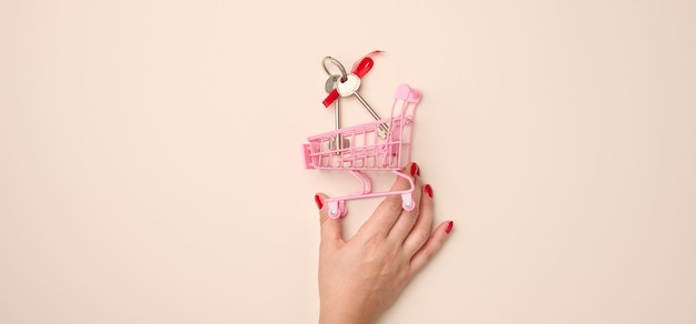 여성의 손은 베이지색 배경에 열쇠가 있는 소형 금속 쇼핑 카트를 들고 있습니다. 부동산 구매, 모기지, 할인, 배너