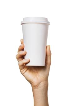 女性の手は、白い背景で隔離の明るい色合いの紙コップを保持します。