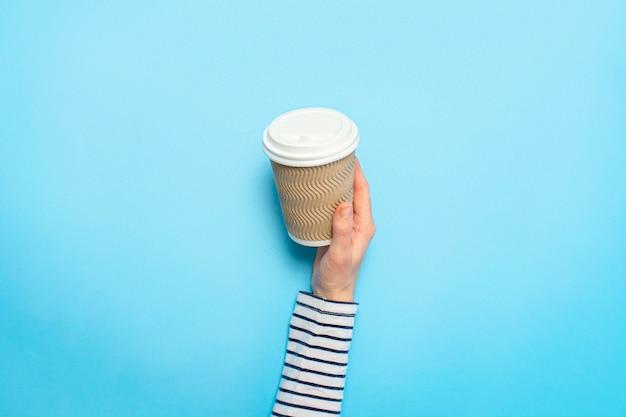 女性の手は、青のコーヒーと紙コップを保持しています。コーヒー、温かい飲み物、朝食の概念。