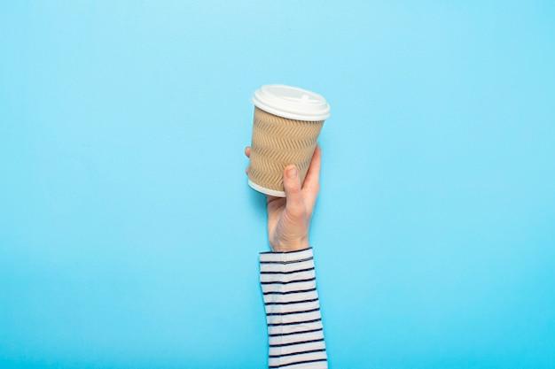 女性の手はコーヒーと紙コップを保持します
