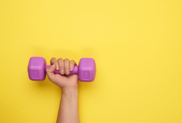 女性の手は黄色、コピースペース、上面図に紫色の1キログラムのダンベルを保持します