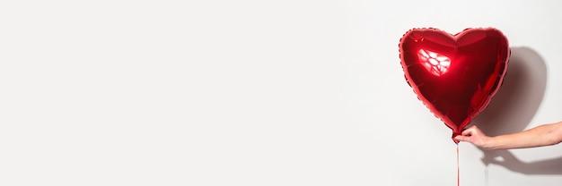 여성 손 흰색 바탕에 심장의 형태로 빨간 공기 풍선을 보유하고있다. 배너.