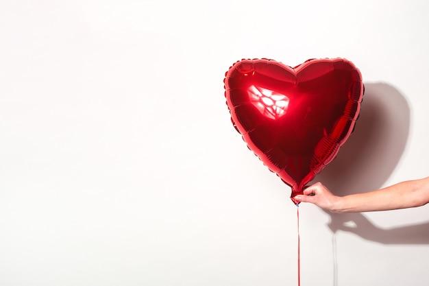 여성 손 흰색 바탕에 심장의 형태로 빨간 공기 풍선을 보유하고있다.