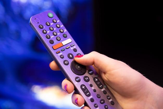 Женская рука держит пульт дистанционного управления smart tv с микрофоном и голосовым управлением