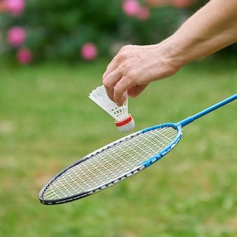 女性の手は、背景に緑の草とピンクの花と白いバドミントンシャトルコックとラケットを屋外で保持しています。屋外のサマーガーデンでアクティブなスポーツゲーム