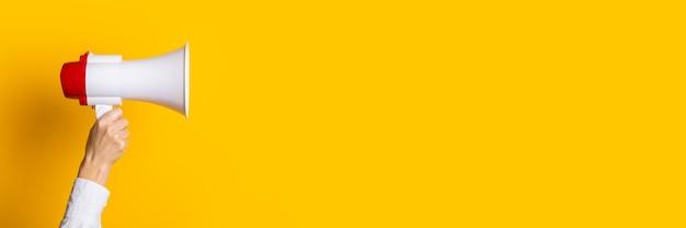 女性の手は黄色の背景に赤いメガホンと白を保持します