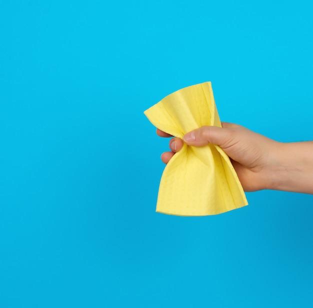 女性の手は、クリーニングのために黄色の布スポンジを保持しています。