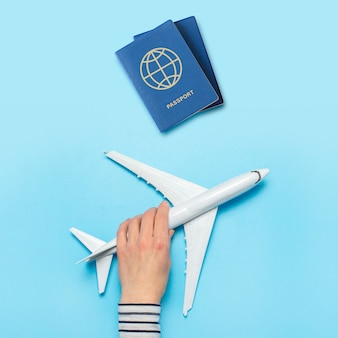 Female hand holds an airplane and passports on a blue space. concept flight, tickets, booking, flight search, travel