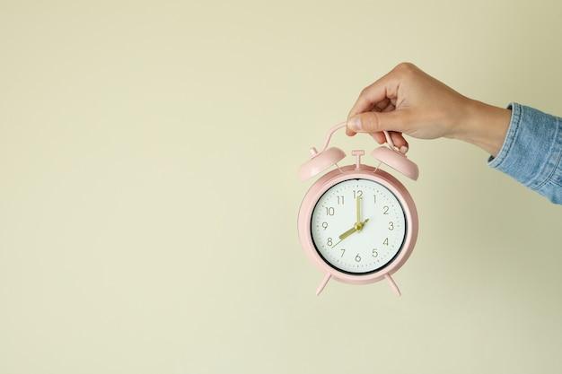 여성 손 베이지 색 바탕에 알람 시계를 보유