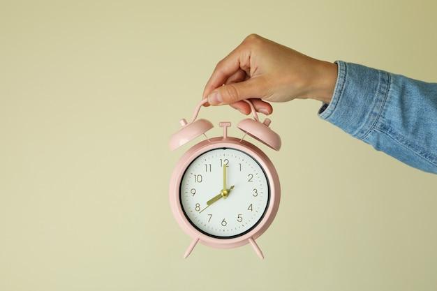 여성 손 베이지 색에 알람 시계를 보유