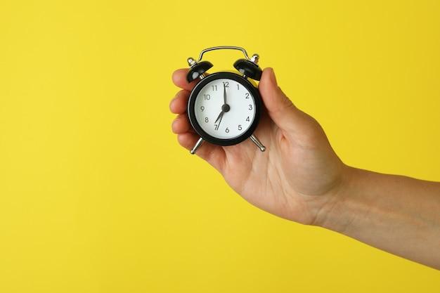 여성 손 노란색에 알람 시계를 보유