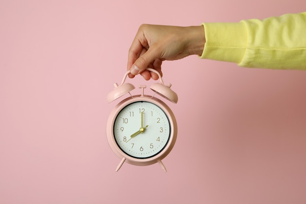 Female hand holds alarm clock on pink surface