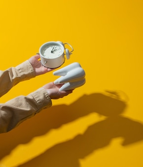 Female hand holds alarm clock next to tooth on yellow surface