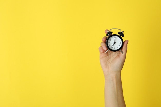 Female hand holds alarm clock on yellow surface