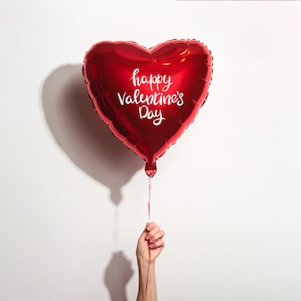 여성 손 흰색 바탕에 비문 해피 발렌타인 데이와 심장의 형태로 공기 풍선을 보유하고있다.