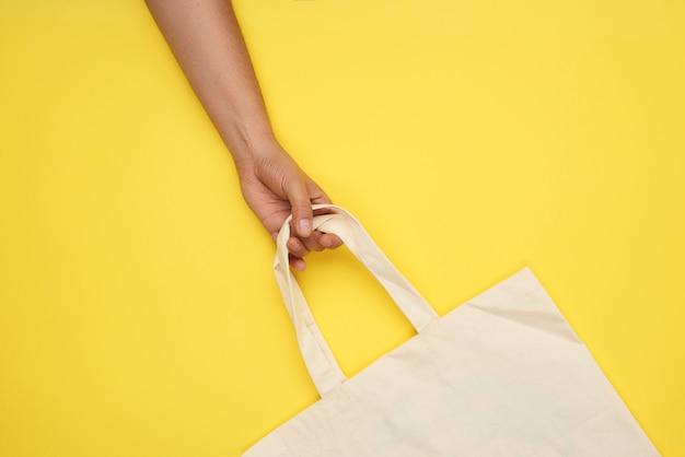Женская рука держит за ручки пустой бежевый текстильный мешок на желтом, отказ от пластиковых пакетов, вид сверху