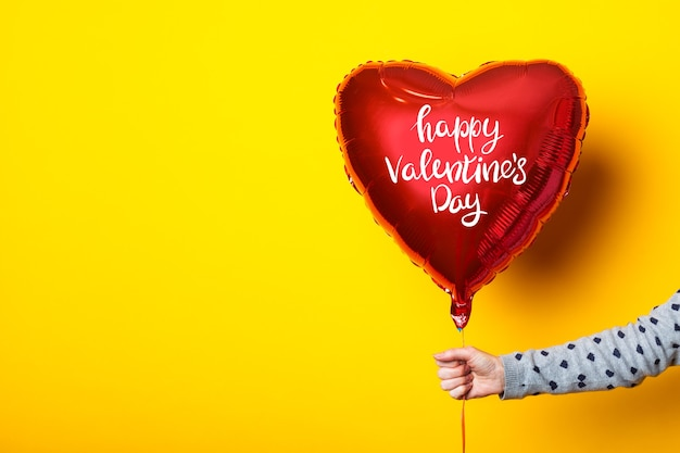 女性の手は、黄色の背景にハッピーバレンタインデーの碑文が付いた膨脹可能なハート型の風船を持っています。